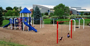 Photo of play equipment at Monica Lucero Park with GCCC in the background